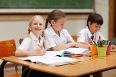 Smiling girl sitting next to schoolfellows Stock Photos