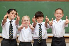 Smiling students in school uniforms giving thumbs up - stock photo