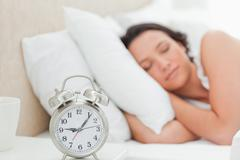 Alarm clock with a woman sleeping Stock Photos