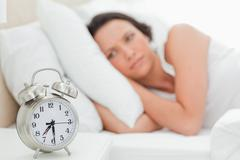 Alarm clock with a woman who just wakes up Stock Photos