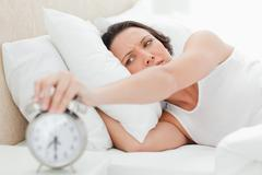 Woman turning off her alarm clock - stock photo