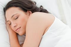 Close-up of a cute woman sleeping - stock photo