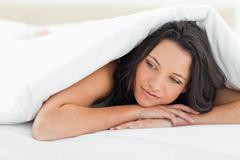 Cute young woman under the duvet - stock photo