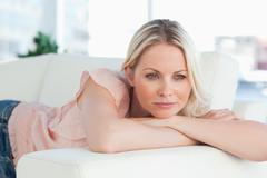 Pink shirt woman lying on her sofa - stock photo