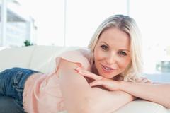 Smiling european woman lying on her sofa - stock photo