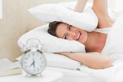 Woman crying while her alarm is ringing Stock Photos