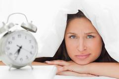 Cute woman who doesn't want to wake up - stock photo