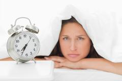 Alarm clock with a woman sulking Stock Photos