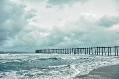 Old jetty over the stormy sea Stock Photos