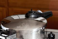 Pressure being released from cooker on hob Stock Photos