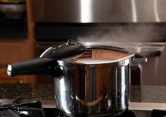 steam escaping from new pressure cooker pot - stock photo