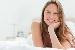 Caucasian woman lying on her bed Stock Photos