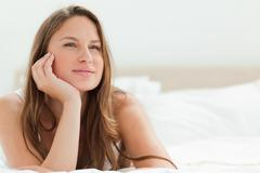 Stock Photo of Portrait of a calm woman lying on her bed