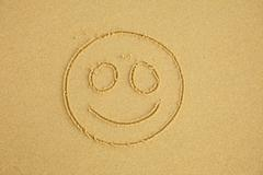 Smiling face on sand Stock Photos