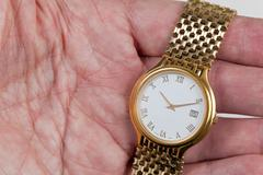 Gold watch with white face in palm of hand Stock Photos