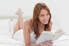 Redheaded lying on her bed while holding a book Stock Photos