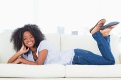 Stock Photo of Portrait of a cool brown woman lying on her sofa