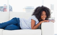 Portrait of a smiling woman lying on her sofa - stock photo