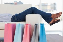 Woman lying on her sofa with shopping bags on the floor Stock Photos