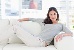 Portrait of a charming woman lying on her divan Stock Photos