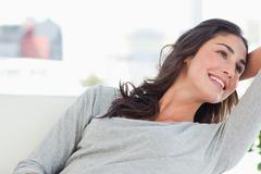 Stock Photo of Portrait of a beaming woman lying on her sofa