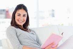 Portrait of a smiling woman with a novel - stock photo