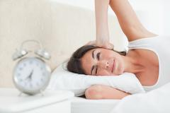 Brunette waking up by her alarm - stock photo