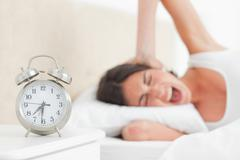 Upset brunette waking up by her alarm Stock Photos