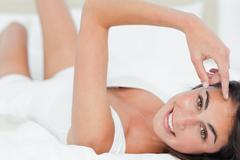 Stock Photo of Portrait of a cute brunette lying on her back