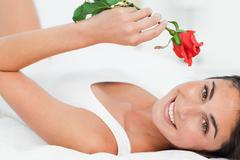Stock Photo of Portrait of a brunette lying on her back while holding a rose