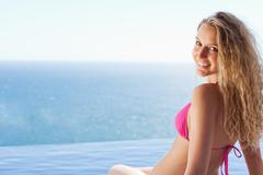 Stock Photo of Young woman sitting on the pool edge