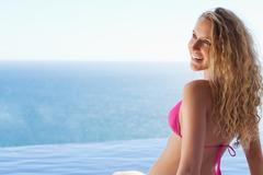 Stock Photo of Smiling woman sitting on the pool edge