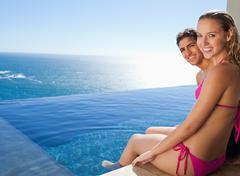 Smiling couple sitting on the pool edge Stock Photos