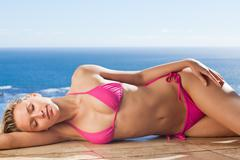 Stock Photo of Woman enjoying the sun while lying on the pool edge