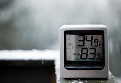 snow falling behind thermometer - stock photo