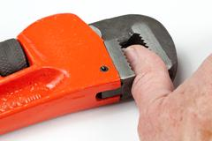 thumb trapped in red wrench - stock photo