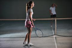 Stock Photo of young girls playing tennis game indoor