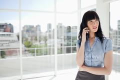 Businesswoman talking on the phone and looking towards the side Stock Photos