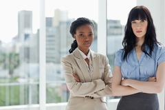 Two serious businesswomen looking at camera with a focus look Stock Photos