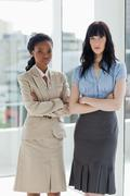 Two serious businesswomen standing upright with their arms crossed Stock Photos