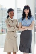Stock Photo of Two businesswomen standing upright with a smiling face