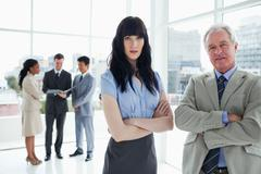 A mature businessman and a young serious woman standing upright Stock Photos