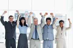 Stock Photo of Five business people showing their approval with their arms raised above their
