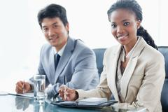 Two smiling employees which are working Stock Photos