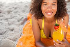 Young smiling woman lying on a beach towel while holding a fruit cocktail - stock photo