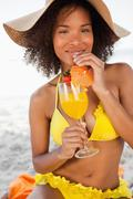 Stock Photo of Young smiling woman drinking a fruit cocktail while wearing a yellow swimsuit