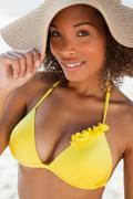 Stock Photo of Young attractive woman standing on the beach while holding her hat brim