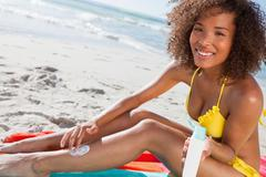 Young beautiful woman applying sunscreen on her leg while holding the bottle - stock photo