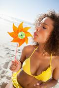 Young woman standing in beachwear while blowing on a pinwheel - stock photo