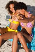 Young woman photographing herself and a friend while sitting on the beach - stock photo